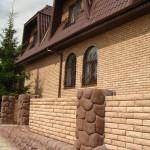 дом из рваного кирпича с забором