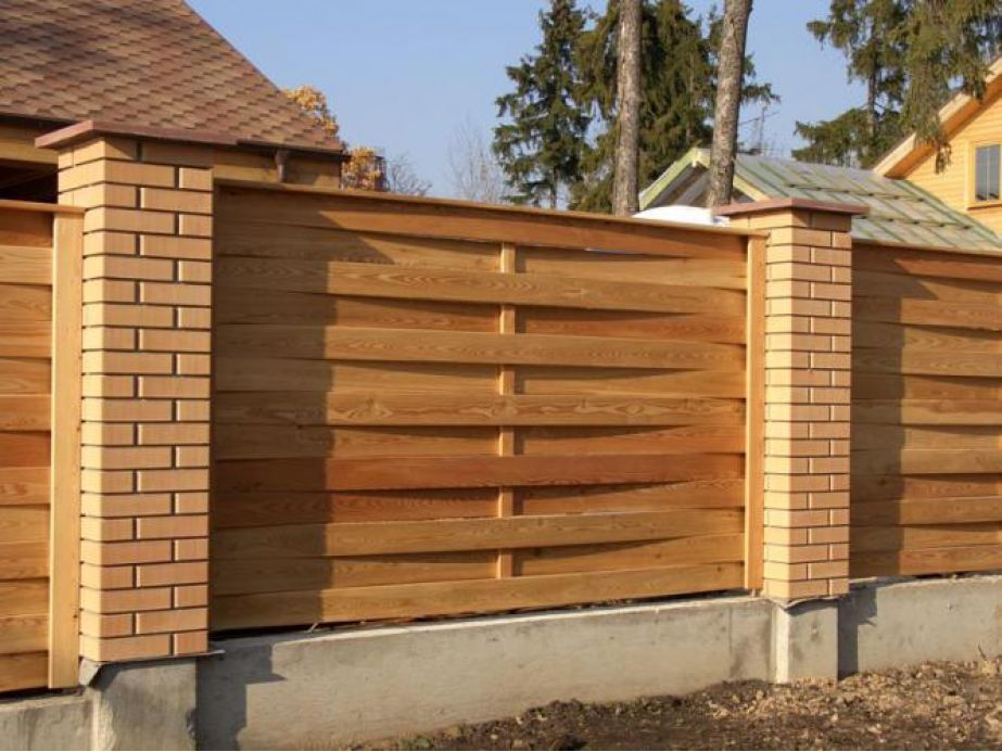 Забор, построенный из кирпича и дерева фото